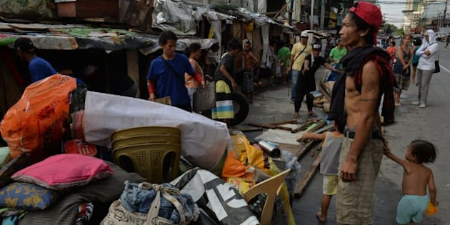 A father holds his children next to their belongings as he watches workers demolished their makeshift house erected along pedestrian lane on a street in Quezon City suburban Manila on September 29, 2015, as city officials intensified its campaign against illegal structures along pedestrian lanes and streets, blocking the flow of traffic. Traffic jams in the Philippine capital of 12 million have worsened in recent months, as the government rushed to build elevated tollways to accommodate the growing number of vehicles acquired amid a booming economy, but roughly one quarter of the nation's 100 million people live in poverty, which is defined as surviving on about one dollar a day. AFP PHOTO / TED ALJIBE        (Photo credit should read TED ALJIBE/AFP/Getty Images)