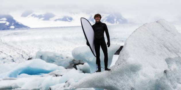Caucasian surfer carrying board near glacial water