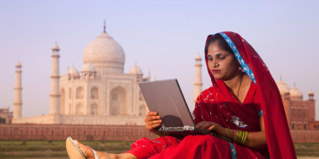 Indian woman in red sari using laptop at sunrise with Taj Mahal in distance