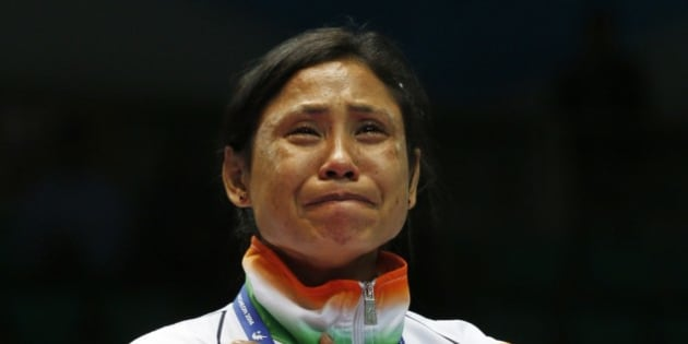 FILE - In this Oct. 1, 2014 file photo, India's L. Sarita Devi cries after she refused her bronze medal during the medal ceremony for the women's light 60-kilogram division boxing at the 17th Asian Games in Incheon, South Korea. The Indian female boxer who had refused to accept her bronze medal at the Asian Games has been banned for one year backdated to the day of the incident on Oct. 1, Boxing India said Wednesday, Dec. 17, 2014. Devi was angered by the judging in her semifinal loss in the 60-kilogram division and showed her displeasure in the medal ceremony, refusing to let the medal be placed around her neck. (AP Photo/Kin Cheung, File)