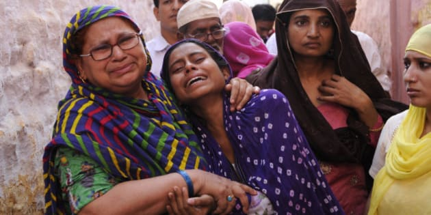 GREATER NOIDA, INDIA - SEPTEMBER 29: Family members of Mohammad Akhlaq (50-year-old man) mourn during his funeral at their village in Bisada on September 29, 2015 in Greater Noida, India. Akhlaq was beaten to death and his son critically injured by a mob over an allegation of storing and consuming beef at home, late night on Monday, in UPs Dadri. Police and PAC were immediately deployed in the village to maintain law and order. Six persons were arrested in connection with the killing of man. (Photo by Burhaan Kinu/Hindustan Times via Getty Images)