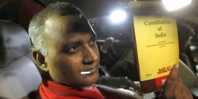 NEW DELHI, INDIA - SEPTEMBER 28: AAP MLA Somnath Bharti shows a book of Constitution of India as he arrives to surrender at the Dwarka North Police Station on September 28, 2015 in New Delhi, India. Somnath Bharti, who has been evading arrest for nearly a week, surrendered before police tonight hours after the Supreme Court ordered him to give up by evening in the domestic violence and attempt to murder case filed by his wife. (Photo by Vipin Kumar/Hindustan Times via Getty Images)