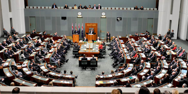 New Zealand's Prime Minister John Key, standing before flags, addresses a joint sitting of the Australian parliament in the House of Representatives chamber at Parliament House in Canberra, Australia, Monday, June 20, 2011. (AP Photo/Alan Porritt, Pool)