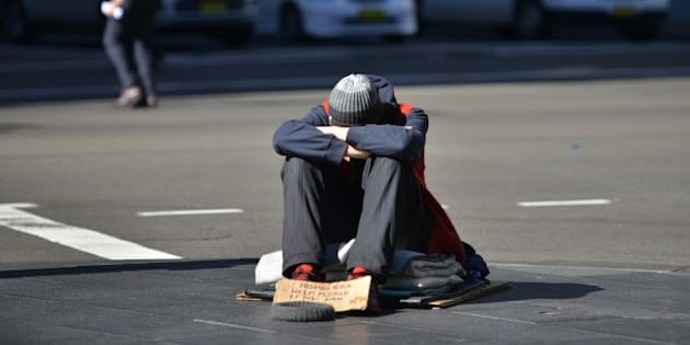 A homeless man sits on a street in the Central Business District of Sydney as the Australian government prepares to release its 2015/16 budget on May 12, 2015.  Australian Treasurer Joe Hockey insisted he will deliver a 'responsible and fair' budget as the government battles to juggle slumping revenue and a huge deficit while avoiding a voter backlash. AFP PHOTO/Peter PARKS        (Photo credit should read PETER PARKS/AFP/Getty Images)