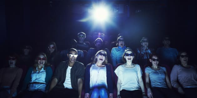 Group of people wearing 3D glasses at the movies