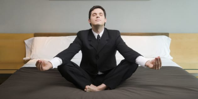 Businessman meditating on the bed in a hotel room