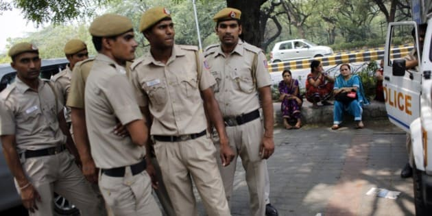 Delhi policemen stand guard as members of All India Democratic Women's Association (AIDWA) sit on a pavement at the end of a protest against the gang rape of two teenage girls, in New Delhi, India, Saturday, May 31, 2014. Police arrested a third suspect and hunted for two others Saturday in the gang rape and slaying of two teenage cousins found hanging from a tree in Katra village, in the northern Indian state of Uttar Pradesh, a case that has prompted national outrage. (AP Photo/Altaf Qadri)
