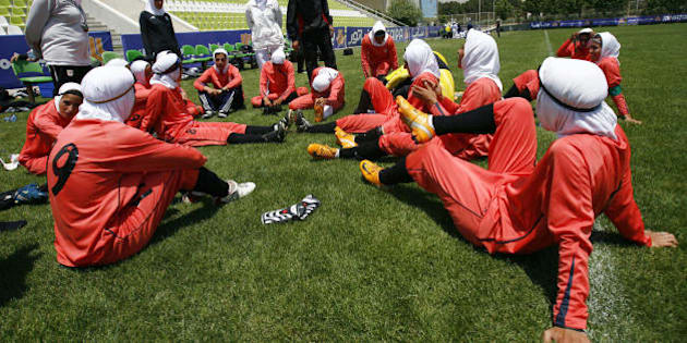 Players of Iran's women national football team listen to instructions before their friendly football match with club Malavan Anzali women's team in Tehran on June 25, 2009. The head of Iran's football federation has denied punishing players for wearing green wristbands in a show of support of the opposition during a World Cup qualifier, local media reported. AFP PHOTO/ISNA/AMIR POORMAND (Photo credit should read Amir Poormand/AFP/Getty Images)
