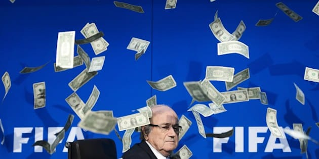 FIFA president Sepp Blatter looks on as fake dollar notes fly around him, thrown by a British comedian during a press conference at the FIFA world-body headquarter's on July 20, 2015 in Zurich. The 79-year-old Swiss official looked shaken as the notes thrown by Simon Brodkin, stagename Lee Nelson, fluttered around him in a conference hall at the FIFA headquarters. Brodkin was taken away in a Swiss police car after the stunt. AFP PHOTO / FABRICE COFFRINI        (Photo credit should read FABRICE COFFRINI/AFP/Getty Images)