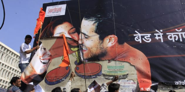 Indian supporters of the Hindu right wing Sanskriti Bachao (Save the Culture) organisation tear down a poster advertising condoms in Bhopal  on January 14, 2010.  The right wing outfit in central India has ordered shopkeepers to remove lingerie advertisements and mannequins displaying undergarments while condemning condom advertisements as they consider them to be obscene and against traditional Indian values.  AFP PHOTO/STR (Photo credit should read STR/AFP/Getty Images)
