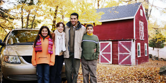 Parents standing beside car with son and daughter (12-14), portrait