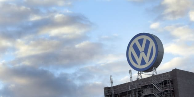 A giant logo of the German car manufacturer Volkswagen is pictured on top of a company's factory building in Wolfsburg, Germany, Saturday, Sept. 26, 2015. (AP Photo/Michael Sohn)