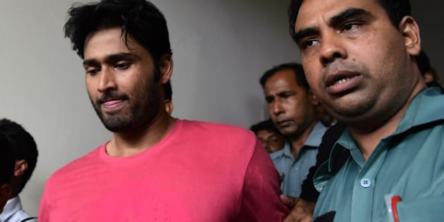 Bangladeshi security personnel escort fugitive cricketer Shahadat Hossain (C) after he surrendered in Dhaka on October 5, 2015. Hossain was remanded in jail on October 5 shortly after he surrendered to a court over allegations of beating his 11-year-old maid, his lawyer said. AFP PHOTO / MUNIR UZ ZAMAN        (Photo credit should read MUNIR UZ ZAMAN/AFP/Getty Images)