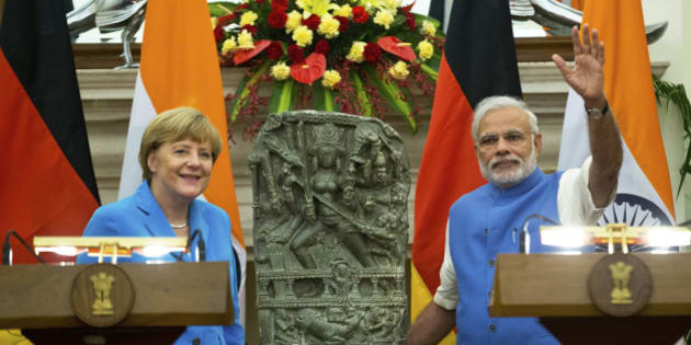 German Chancellor, Angela Merkel, left, and Indian Prime Minister Narendra Modi pose for a photograph with a 10th centery idol of Hindu Goddess Durga, that was returned by Germany, in New Delhi, India, Monday, Oct. 5, 2015. Merkel is on a three-day visit to India. (AP Photo/Saurabh Das)