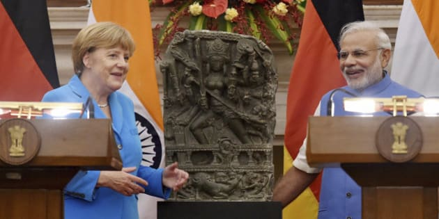 German Chancellor Angela Merkel, left and Indian Prime Minister Narendra Modi, pose  with a tenth century idol of Hindu goddess Durga, that was returned by Germany in New Delhi, India, Monday, Oct. 5, 2015. Merkel is on a three-days official visit to India. (Atul Yadav/ Press Trust of India via AP) INDIA OUT