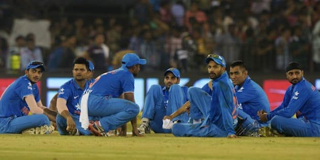 India's captain Mahendra Singh Dhoni (2R) sits with teammates as play is interrupted by spectators throwing bottles onto the pitch during the second T20 cricket match between India and South Africa at The Barabati Stadium in Cuttack on October 5, 2015. AFP PHOTO / DIBYANGSHU SARKAR --IMAGE RESTRICTED TO EDITORIAL USE - STRICTLY NO COMMERCIAL USE--        (Photo credit should read DIBYANGSHU SARKAR/AFP/Getty Images)