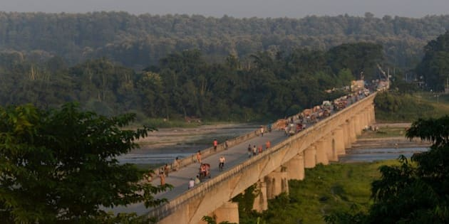 People walk over a bridge at an entry point to Nepal from India at Mechinagar on the eastern Nepalese border with India on September 30, 2015. A Nepali lawmaker, tipped to be the next prime minister, accused neighbouring giant India September 30 of deliberately blocking vital supplies into the landlocked country, as the government announced fresh fuel restrictions. Scores of Indian trucks have been stranded at a key border checkpost for almost a week, halting fuel and other supplies, following protests by ethnic minorities over the Himalayan nation's new constitution. AFP PHOTO / Diptendu DUTTA        (Photo credit should read DIPTENDU DUTTA/AFP/Getty Images)