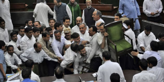 State lawmakers of the opposition People's Democratic Party scuffle with staff members of the house after a controversial bill was passed in the Jammu and Kashmir Assembly in Jammu, India, Friday, April 9, 2010. According to the new bill, an educated youth can now apply for government jobs only in his own district whereas a youth belonging to lower castes can apply for the same in any of 22 district in the state including Kashmir valley, according to a news agency. (AP Photo)