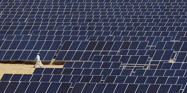 TO GO WITH: Climate-warming-COP21-India-energy-solar, FOCUS by Annie Banerji In this photograph taken on August 23, 2015, an Indian worker walks past lines of solar panels at Roha Dyechem solar plant at Bhadla some 225 kms north of Jodhpur in the western Indian state of Rajasthan.   Under a blistering sun, workers install a sea of solar panels in a north Indian desert as part of the government's clean energy push --- and its trump card at upcoming climate change talks in Paris.  AFP PHOTO/MONEY SHARMA        (Photo credit should read MONEY SHARMA/AFP/Getty Images)