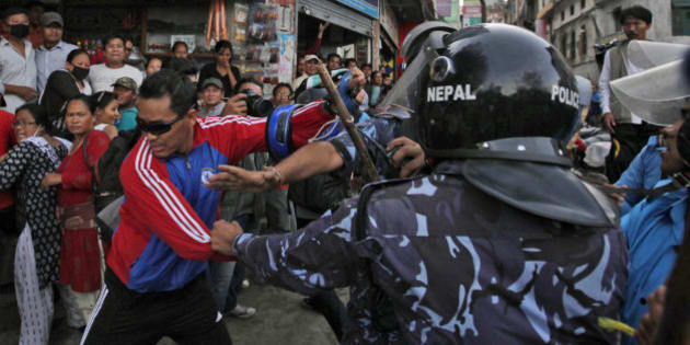 Nepalese protesters try to clash with policemen after burning a copy of the new constitution during the protest organized by splinter of the Maoist party, alliance of ethnic group and Madhesi party, in Kathmandu, Nepal, Monday, Sept. 21,2015. Nepal on Sunday, Sept. 20, 2015, formally adopted a much anticipated and long-delayed constitution that took more than seven years to complete following a decade of political infighting. However, security was stepped up across the nation, with smaller political parties and ethnic groups opposing to the new charter and fighting for equal representation in the country's political structure, which according to them has failed to meet their aspirations. (AP Photo/Niranjan Shrestha)