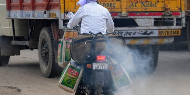 In this photograph taken on February 25, 2015, an Indian motorcyclist rides with smoke belching from his machine in New Delhi, ahead of World Environment Day which falls on June 5.   The Indian government is under intense pressure to act after the World Health Organization last year declared New Delhi the world's most polluted capital.  At least 3,000 people die prematurely every year in the city because of air pollution, according to a joint study by Boston-based Health Effects Institute and Delhi's Energy Resources Institute.  AFP PHOTO/ MONEY SHARMA        (Photo credit should read MONEY SHARMA/AFP/Getty Images)