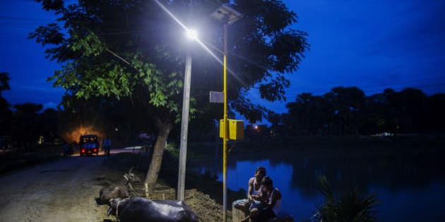Cows rest by the side of a road as a man and child sit under a light powered by energy from a solar power microgrid at night in the village of Dharnai in Jehanabad, Bihar, India, on Thursday, July 9, 2015. While Prime Minister Narendra Modi's ambition has led billionaires such as Foxconn Technology Group's Terry Gou to pledge investment, the question remains whether the 750 million Indians living on less than $2 per day can afford or will embrace green energy. Photographer: Prashanth Vishwanathan/Bloomberg via Getty Images
