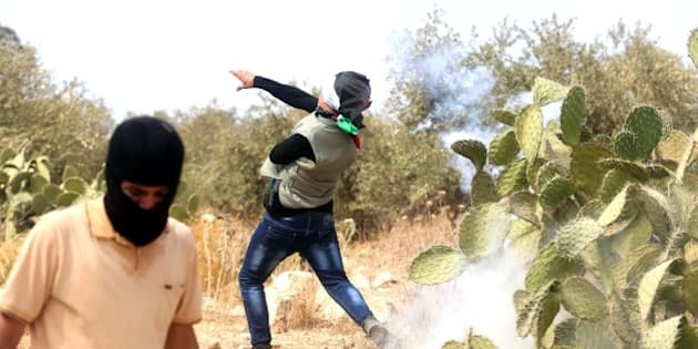 RAMALLAH, WEST BANK - OCTOBER 02: Palestinian protesters throw stones as a response to the Israeli forces attack during a demonstration after the Friday Prayer against Israeli Government's violations over Al-Aqsa Mosque, on October 02, 2015in Badrus village of Ramallah, West Bank. (Photo by Issam Rimawi/Anadolu Agency/Getty Images)