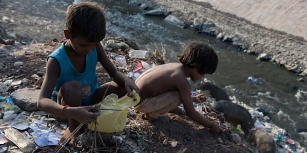 Indian boys Chandan (L), 6, and Badar, 5, sort through waste on the banks of a small polluted tributary flowing into the River Ganges, as they look for bits of scrap metal   they can sell for a few rupees in Varanasi on September 16, 2015. The Ganges is heavily polluted with raw sewage, animal and human corpses, and industrial waste entering the waterway, which is considered holy in Hindu-majority India. Millions of children work long hours often in poor conditions in the south Asian giant, where almost a quarter of the 1.2 billion population lives on less than USD 1.25 a day. AFP PHOTO / ALEX OGLE        (Photo credit should read Alex Ogle/AFP/Getty Images)
