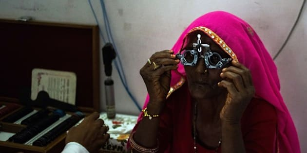 In this photograph taken on August 14, 2014, an Indian patient adjusts a pair of glasses used to test eyesight during an examination at the Dr Shroff Charity Eye Hospital Vision Centre in Thanagazi, some 47 kms from Alwar in the state of Rajasthan. India's Dr Shroff Charity Eye Hospital operates a network of hospitals and vision centres in towns and villages in the states of Haryana, Uttar Pradesh and Rajasthan, and in the capital New Delhi, in an attempt to tackle avoidable blindness. Offering low-cost or pro-bono treatment for conditions like cataracts and glaucoma, staff travel to remote areas to provide check-ups at field camps, and work in vision centres in towns and villages, referring certain cases to larger hospitals. The Shroff network aims extend access to low-cost, high-quality eye care to those who might not normally be able to access or afford it. More women than men suffer problems with eyesight, according to staff at the Dr Shroff Charity Eye Hospital, because of the societal roles they take on. Women traditionally spend a greater amount of time working outdoors, exposed to harsh sunlight and UV rays. They often feed male family members and children first, consuming less-nutritious meals after others have eaten, and cook over naked flames where they exposed to smoke from animal dung, leaves or coal used as fuel. Women also earn less, and live in more unhygienic conditions which can lead to infections, while male family members often relocate to towns or cities for work, where conditions and salaries are better. The World Health Organisation estimates four in five cases of blindness globally are avoidable. World Sight Day is marked in 2014 on October 9, and calls for 'No More Avoidable Blindness'. AFP PHOTO/Rebecca Conway        (Photo credit should read Rebecca Conway/AFP/Getty Images)