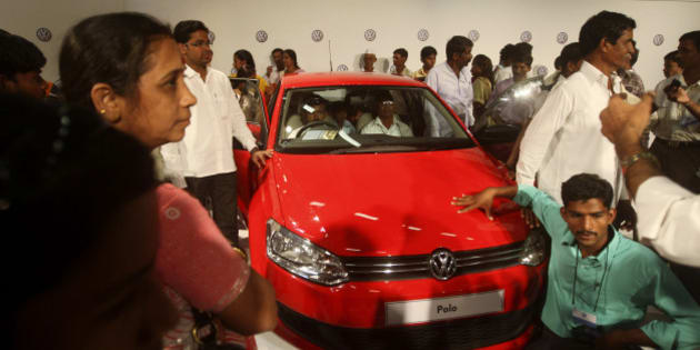 """People take a closer look of a Volkswagen Polo at its new factory in Chakan, near Pune, India, Saturday, Dec. 12, 2009. Volkswagen rolled out its first India made Polo Saturday. Volkswagen AG started production of its first compact car in India on Saturday, hoping to capture up to 10 percent of the country's fast-growing automobile market within the next six years, the company said. The factory, opened earlier this year, is part of a 580 million euros (US$846.8 million) investment, which the company says is a """"key element"""" in its India strategy. (AP Photo/Rafiq Maqbool)"""
