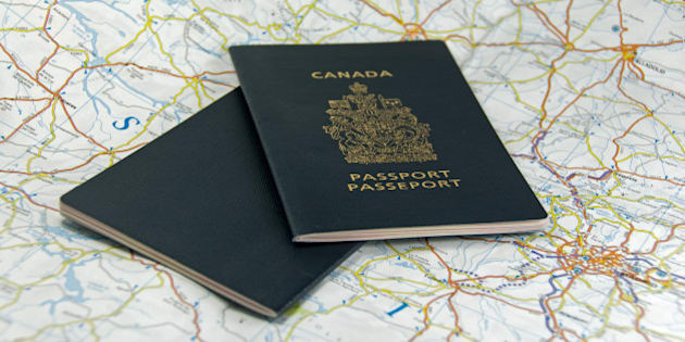 A pair of closed Canadian Passports laid upon a map.