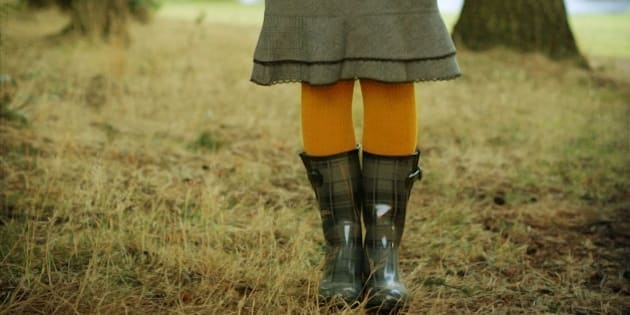 Woman wearing gray rainboots and yellow tights in forest clearing.