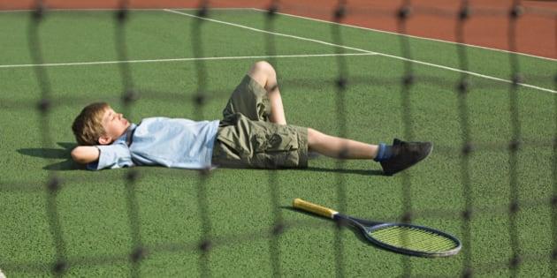 Boy lying on tennis court