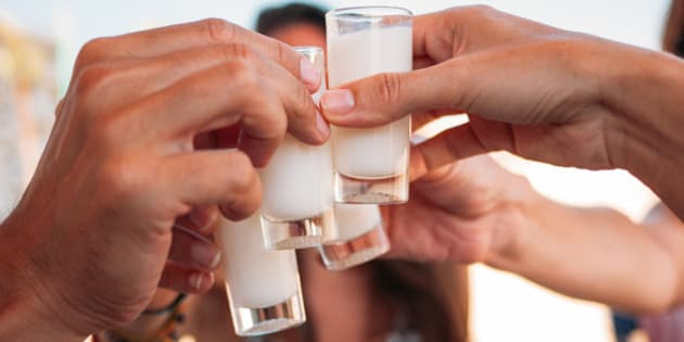 Friends rising shot glasses of rice cream liqueur