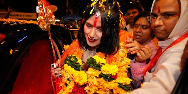 MUMBAI, INDIA - AUGUST 27: (file photo) Radhe Maa, self-proclaimed Godwoman, visits Siddhivinayak Temple, Prabhadevi, on August 27, 2012 in Mumbai, India. Radhe Maa has been accused of dowry harassment by a woman, who has filed an FIR or police complaint in Mumbai. The woman has said that her husband's family tortured her on the Godwoman's advice and forced her to serve Radhe Maa, do chores for her and give her massages. Radhe Maa's real name is Sukhvinder Kaur. She was born on 4 April 1965 in Dorangala village of Gurdaspur district in Punjab. Her followers state that she was drawn to spirituality as a child, and spent a lot of time at the Kali temple in her village. However, according to the people of her village, she did not show any spiritual leanings as a child. At the age of 23, she became a disciple of Mahant Ram Deen Das of 1008 Paramhans Bagh Dera Mukerian in Hoshiarpur district. Ram Deen Das oversaw her deeksha (initiation ceremony), and gave her the title Radhe Maa. She is usually seen in glittering red bridal wear, heavy jewellery and layers of make-up. Thick garlands and a trident complete the picture. She used to stitch clothes to support her husband's small income. (Photo by Vijayanand Gupta/Hindustan Times via Getty Images)