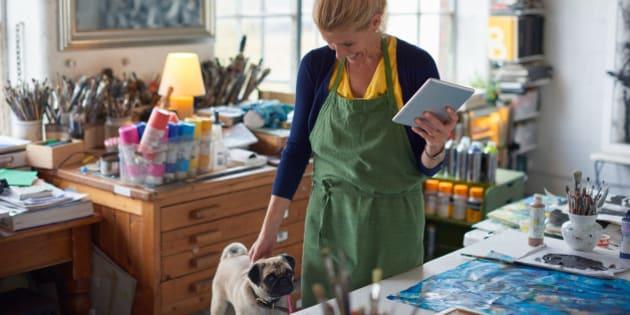 Female designer in her studio holding a digital tablet and stroking her dog