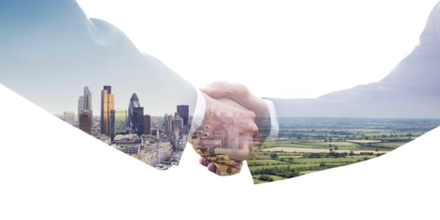 A double exposure of two business men shaking hands with a view of the City of London and of a green fields landscape.