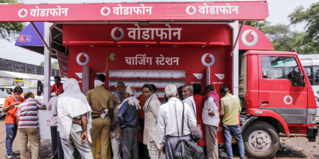 People stand at a Vodafone India Ltd. mobile charging station in Nashik, Maharashtra, India, on Saturday, Sept. 12, 2015. Millions of pilgrims in a landscape awash in saffron make their way to the waters of the holy Godavari River for the Kumbh Mela, the festival of the pitcher. It is one of the largest religious festivals on the face of the planet. Photographer: Dhiraj Singh/Bloomberg via Getty Images