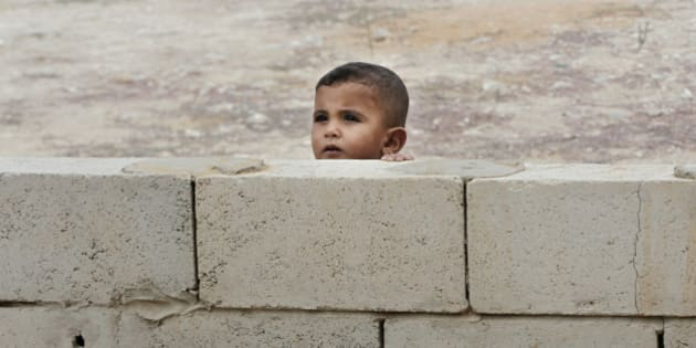 A Syrian boy peeks from behind a wall near a mobile clinic at a refugee camp in the southern town of Zahrani, south of the port city of Sidon, Lebanon, Monday, Sept. 7, 2015. There are some 1.2 million registered Syrian refugees in Lebanon, many of them living in flimsy tents scattered across the country. (AP Photo/Bilal Hussein)