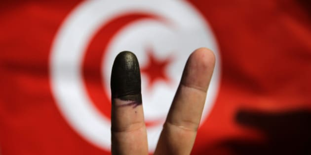 A Tunisian man shows his ink-stained finger in front of a Tunisian flag after voting for the country's parliamentary elections outside the Tunisian embassy in Cairo, Egypt, Saturday, Oct. 25, 2014. On Sunday, Tunisians will vote for their first five-year parliament since they overthrew dictator Zine El Abidine Ben Ali, marking the end of the democratic transition that they alone among the pro-democracy Arab Spring uprisings have managed to achieve. Now, many Tunisians are expressing disillusionment over democracy. (AP Photo/Hassan Ammar)