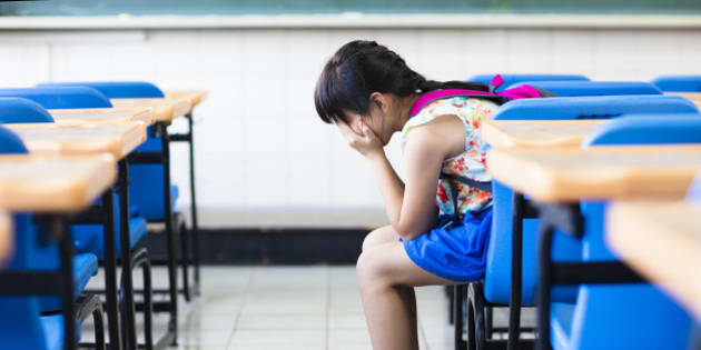 sad girl sitting and  thinking in the classroom