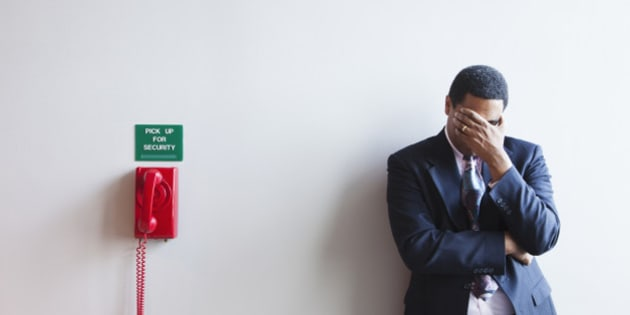 African American businessman leaning against wall covering his face