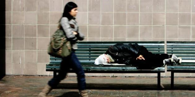 Ausralia, Sydney, homeless man sleeping on a bench, passer-by