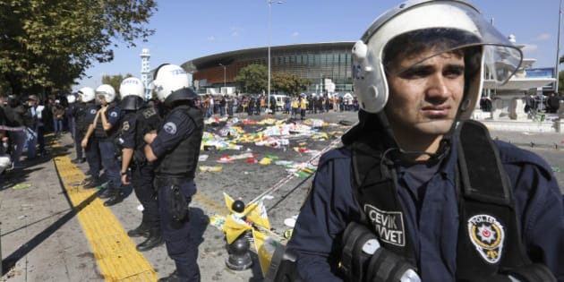 Turkish police officers secure the area at the site of an explosion, where the bodies of victims were covered with flags and banners,  in Ankara, Turkey, Saturday, Oct. 10, 2015. The two bomb explosions targeting a peace rally in the capital Ankara has killed dozens of people and injured scores of others. The explosions occurred minutes apart near Ankara's main train station as people were gathering for the rally, organized by the country's public sector workers' trade union and other civic society groups. The rally aimed to call for an end to the renewed violence between Kurdish rebels and Turkish security forces.  (AP Photo/Burhan Ozbilici)