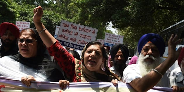 Indian Sikh women shout slogans against the Congress party of India and its President Sonia Gandhi during a protest in New Delhi on June 5, 2015.  The protest was taken against Congress Party leader Jagdish Tytler's alleged role in the 1984 anti-Sikh riots.  AFP PHOTO/ MONEY SHARMA        (Photo credit should read MONEY SHARMA/AFP/Getty Images)