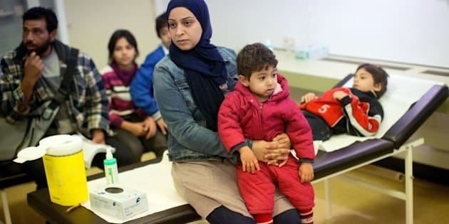 Members of a Syrian refugee family from Damascus wait to get vaccinations at the State Office of Health and Social Affairs (LAGeSo) in Berlin on October 1, 2015. A record 270,000 to 280,000 refugees arrived in Germany in September, more than the total for 2014. The sudden surge this year has left local authorities scrambling to register as well as provide lodgings, food and basic care for the new arrivals.           AFP PHOTO / DPA / KAY NIETFELD    +++  GERMANY OUT   +++        (Photo credit should read KAY NIETFELD/AFP/Getty Images)