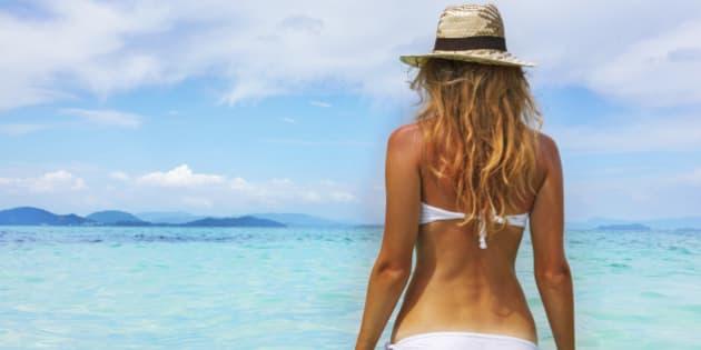 Beautiful young woman in bikini on the sunny tropical beach relaxing in water