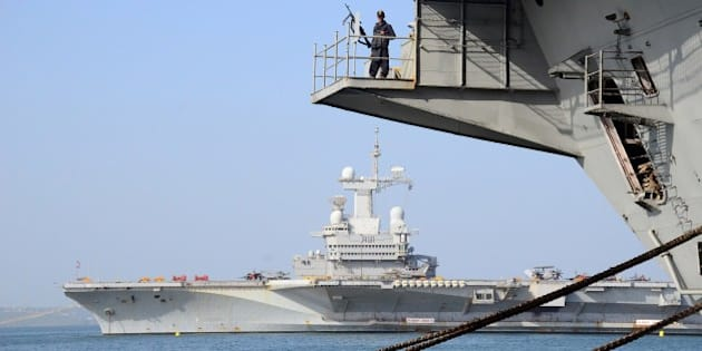In this photograph taken on April 25, 2015, an Indian sailor stands alert on INS Viraat as France's aircraft carrier Charles de Gaulle (REAR) lies off the Indian coast at Goa, ahead of the start of the Indo-French Naval exercise 'Varuna 2015'.  'Varuna 2015' will take place between April 28 and May 3 in the Arabian Sea off the Indian coast.    AFP PHOTO/STR        (Photo credit should read STRDEL/AFP/Getty Images)