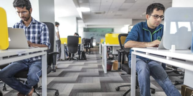 Tiny Owl employees work on laptop computers as pair of sandals sit on the floor inside the company's head office in Mumbai, India, on Monday, March. 9, 2015. Tiny Owl is a smartphone application that helps hungry city-dwellers scour nearby eateries for deliveries. The service now handles 2,000 orders each day and has caught the interest of venture funds including Sequoia Capital, an early backer of technology giants such as Apple Inc. and Oracle Corp. Photographer: Dhiraj Singh/Bloomberg via Getty Images