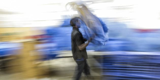 An employee carries a bag during the overnight sort at the Blue Dart Express Ltd. and DHL Express India Pvt. joint hub in Cargo Terminal 3 at Bengaluru International Airport in Bengaluru, India, on Saturday, Feb. 21, 2015. Blue Dart, a unit of DHL Express, is adding a Boeing Co. 757 freighter to its fleet of five in the South Asian country and building warehouses for sellers using portals such as Amazon.com Inc. and Flipkart.com, Malcolm Monteiro, chief executive officer of DHL eCommerce, said in an interview in Mumbai. Photographer: Dhiraj Singh/Bloomberg via Getty Images